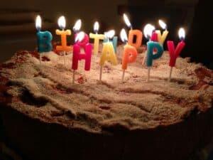 Kerzen auf Kuchen mit Happy Birthday